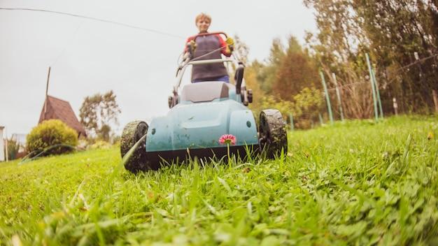 Gelukkig gepensioneerde senior persoon maait een gazon in zijn tuin met een grasmaaier. tuin werk.
