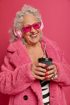 Gelukkig gerimpelde senior vrouw drinkt koffie om te gaan, koptelefoon draagt en muziek luistert