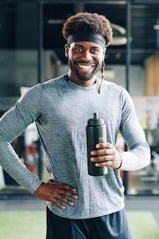 Gelukkig geschikt mensen drinkwater in gymnastiek