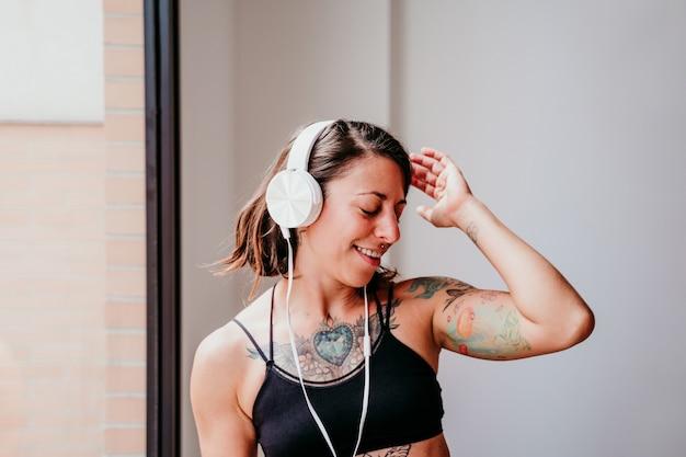 Gelukkig gespierde blanke vrouw luisteren naar muziek op mobiele telefoon en headset in de sportschool. overdag dansen bij het raam. sporten en een gezonde levensstijl