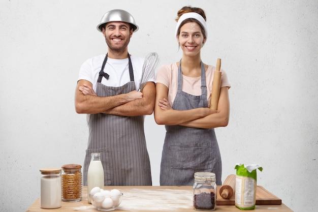 Gelukkig getalenteerde jonge europese familie mannelijke en vrouwelijke koks die schorten dragen en instrumenten vasthouden,