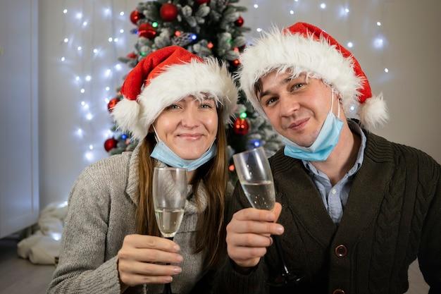 Gelukkig getrouwd stel in beschermende maskers drinkt champagne voor kerstmis.
