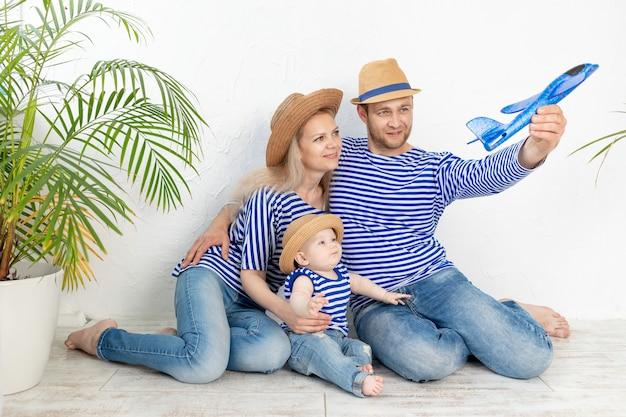 Gelukkig gezin: een moeder, vader en baby in een nautisch beeld in vesten en hoeden lanceren een vliegtuig, het concept van reizen en recreatie