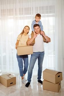 Gelukkig gezin en kind zoon tegen de achtergrond van panoramische ramen. vrouw met kartonnen doos