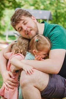 Gelukkig gezin en vaderdag. kind dochters knuffelen vader