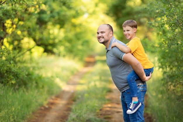 Gelukkig gezin in de zomer: een zoon zit op de rug van zijn vader.