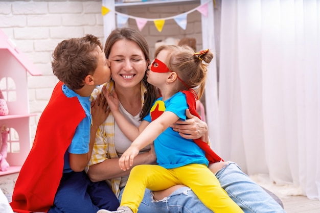 Gelukkig gezin. jonge vrouw speelt met haar kinderen in superhelden.