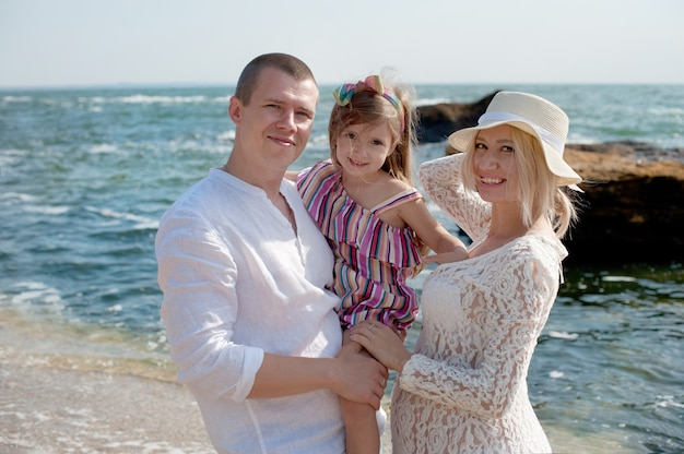 Gelukkig gezin met dochter poseren in de buurt van zee, camera kijken
