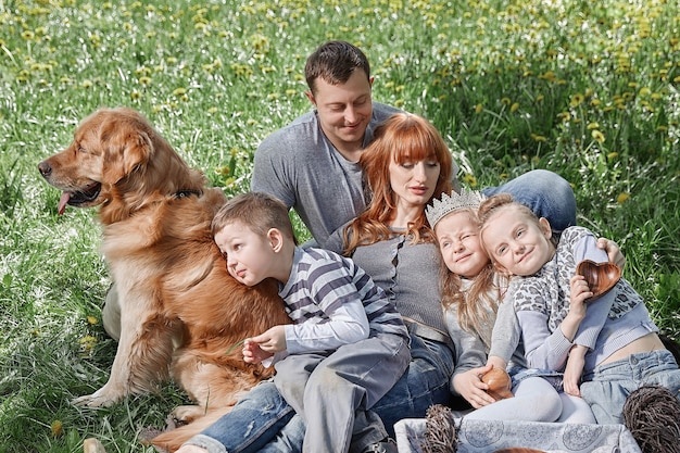 Gelukkig gezin met drie kinderen zittend op het gras in een sunny park