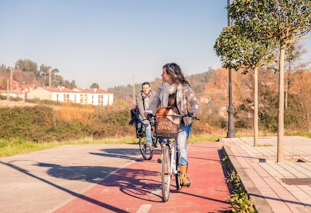 Gelukkig gezin met een dochtertje zittend op een fietsstoeltje fietsen door de natuur op een zonnige winterdag