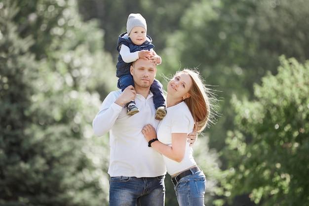 Gelukkig gezin met een jonge zoon op de achtergrond van een zomerpark.