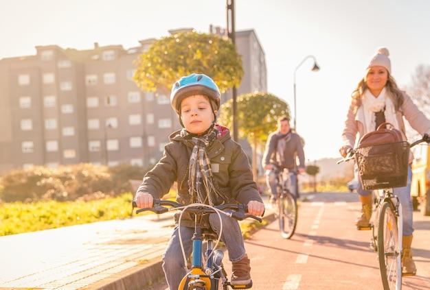 Gelukkig gezin met een kind fietsen door de stad op een zonnige winterdag