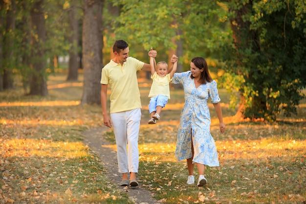 Gelukkig gezin met een klein kind op een wandeling in het park