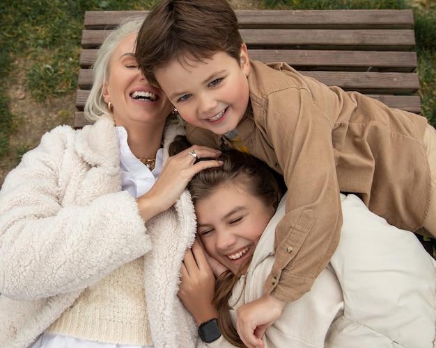 Gelukkig gezin met een ouder buiten op het gras in de herfst, lachende gezichten liggen allemaal met plezier