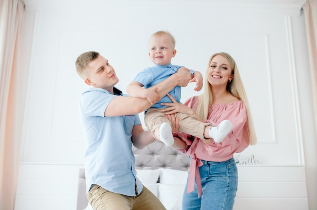 Gelukkig gezin met een schattige baby. moeder, vader, zoon spelen thuis op het bed in een lichte, gezellige kamer.