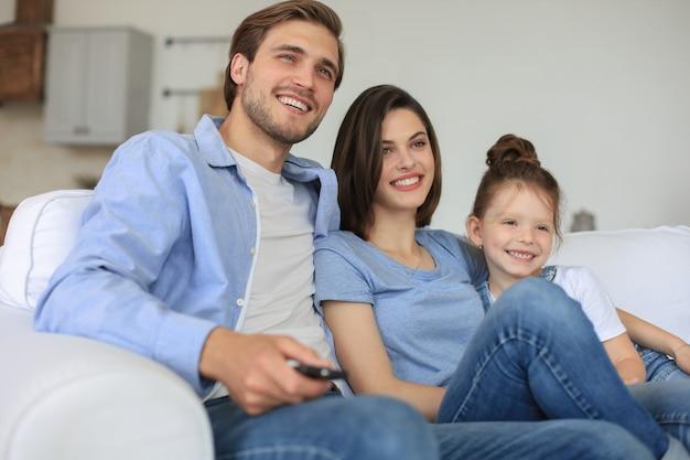 Gelukkig gezin met kind zittend op de bank tv kijken, jonge ouders omarmen dochter samen ontspannen op de bank.