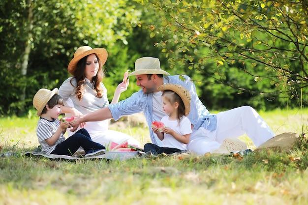Gelukkig gezin met kinderen die picknicken in het park, ouders met kinderen die op tuingras zitten en watermeloen buiten eten