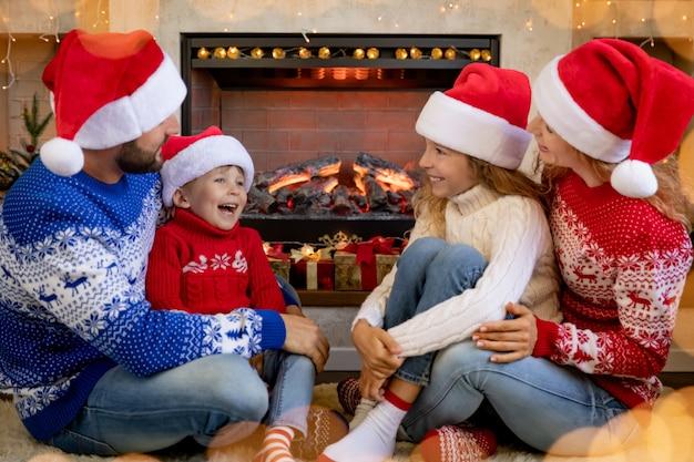 Gelukkig gezin met kinderen in de buurt van open haard met kerstmis. moeder, vader en kinderen hebben plezier thuis.