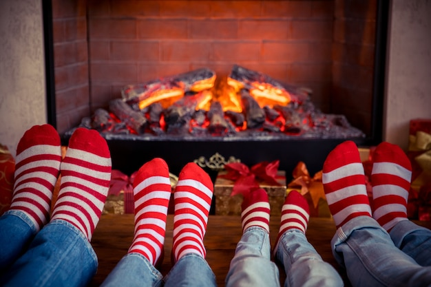 Gelukkig gezin met kinderen in de buurt van open haard met kerstmis. voeten die kerstsokken dragen. winter vakantie concept