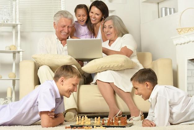 Gelukkig gezin met kinderen op de bank in de woonkamer met laptop, jongens aan het schaken