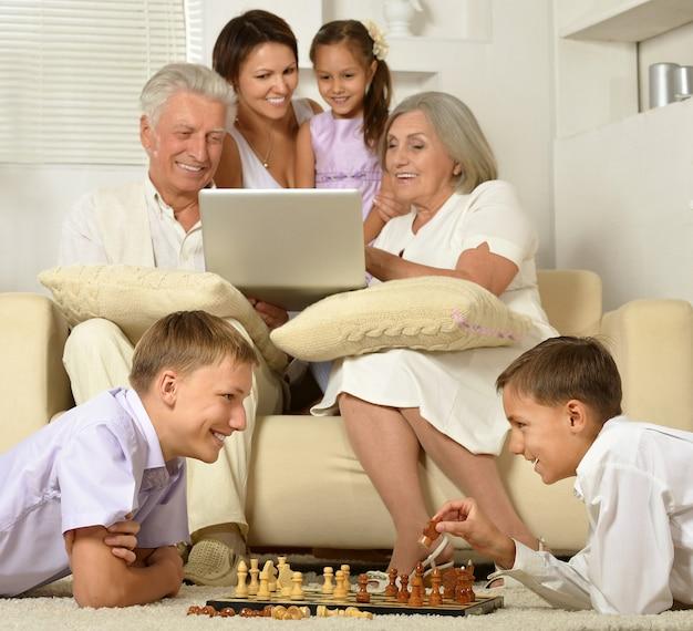 Gelukkig gezin met kinderen op de bank in de woonkamer met laptop