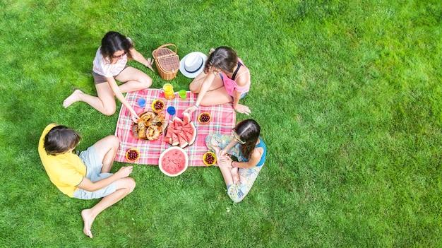Gelukkig gezin met kinderen picknick in het park, ouders met kinderen zittend op het gras van de tuin en gezonde maaltijden buiten eten