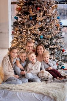 Gelukkig gezin met kinderen plezier en opening presenteert in de buurt van de kerstboom.