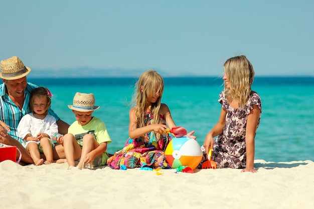 Gelukkig gezin met kinderen spelen op het strand op griekenland in de zomervakantie