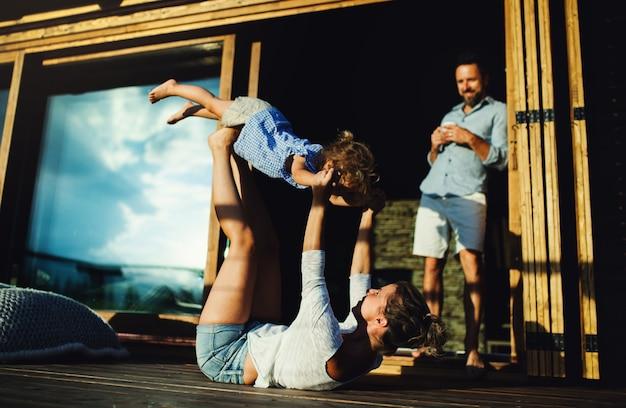 Gelukkig gezin met kleine dochter plezier op terras van houten hut, vakantie in de natuur concept.