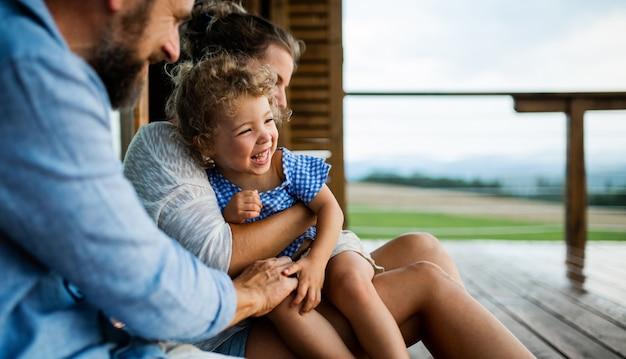 Gelukkig gezin met kleine dochter zittend op terras van houten hut, vakantie in de natuur concept.