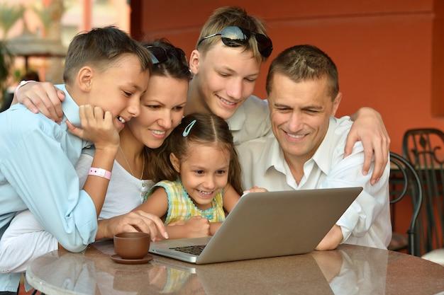 Gelukkig gezin met laptop aan tafel