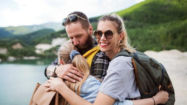 Gelukkig gezin met preteen dochter op wandeltocht op zomervakantie, rusten en knuffelen.