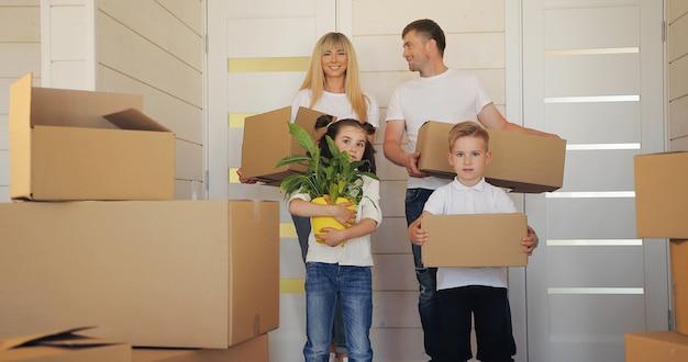 Gelukkig gezin met twee kinderen in het nieuwe huis. moedervader en kind in nieuw huis