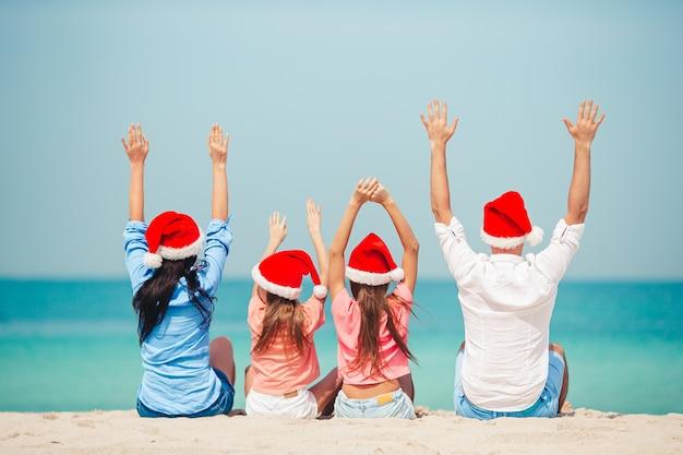 Gelukkig gezin met twee kinderen in kerstmuts op zomervakantie