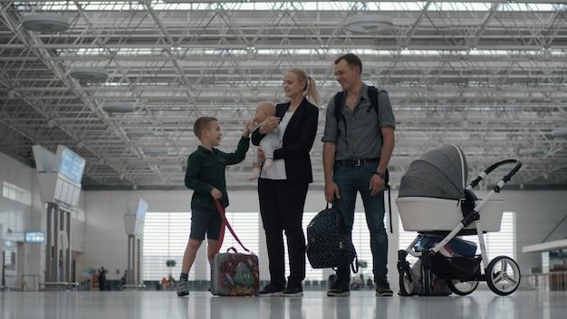 Gelukkig gezin met twee kinderen op de luchthaven Premium Foto