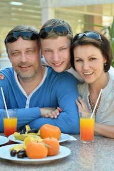 Gelukkig gezin met zoon bij het ontbijt op tafel