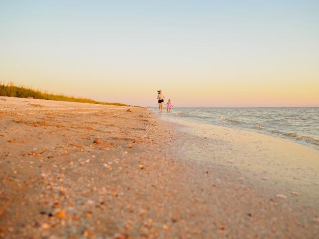Gelukkig gezin - moeder en dochter hebben plezier, rennen langs de zee op een leeg zandstrand. zomervakantie met kinderen