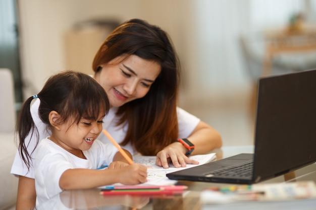 Gelukkig gezin. moeder en dochter schilderen samen. volwassen vrouw helpt het kindmeisje.