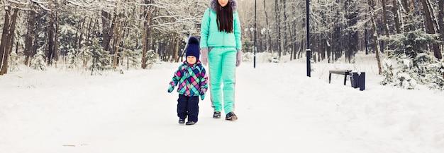 Gelukkig gezin. moeder en kind meisje op een winterwandeling in de natuur. Premium Foto