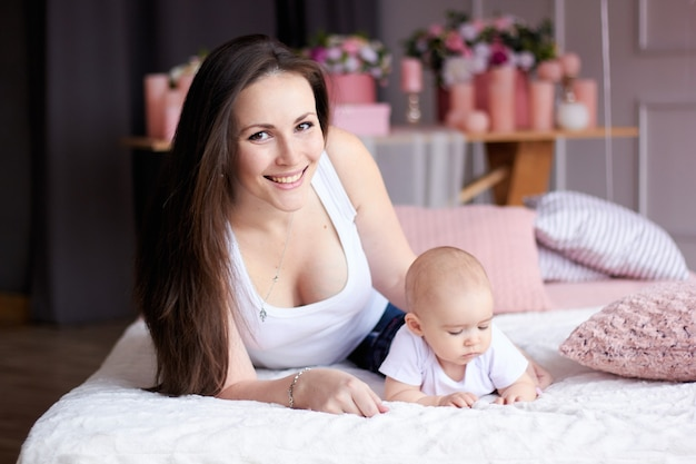 Gelukkig gezin. moeder met haar kleine baby in de slaapkamer
