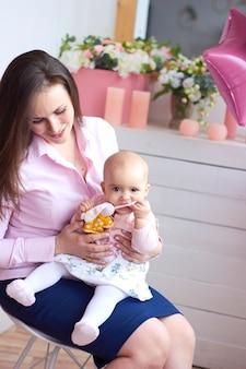 Gelukkig gezin. moeder met haar kleine baby in lichte binnenlandse livihgruimte. moederdagviering met geschenken en bloemen