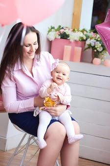 Gelukkig gezin. moeder met haar kleine baby in lichte interieur woonkamer. moederdagviering met geschenken en bloemen