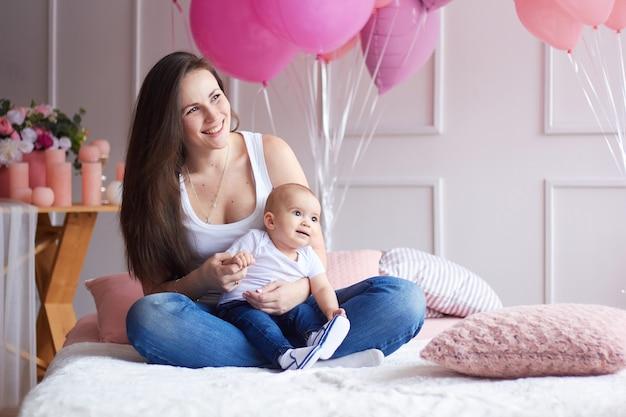 Gelukkig gezin. moeder met haar kleine baby in lichte slaapkamer