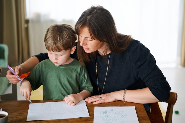 Gelukkig gezin. moeder met zoontje samen schilderen en tekenen. blanke jongen met zijn moeder thuis studeren