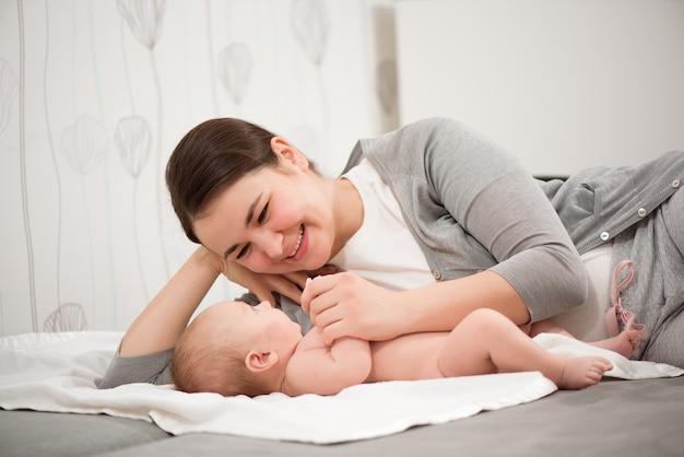 Gelukkig gezin. moeder speelt met haar baby in de slaapkamer.