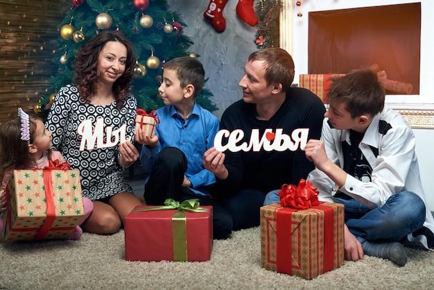 Gelukkig gezin: moeder, vader en drie kinderen bij de open haard voor de wintervakantie. kerstavond en oudejaarsavond. op de foto staan russische letters van het woord: we zijn een familie.