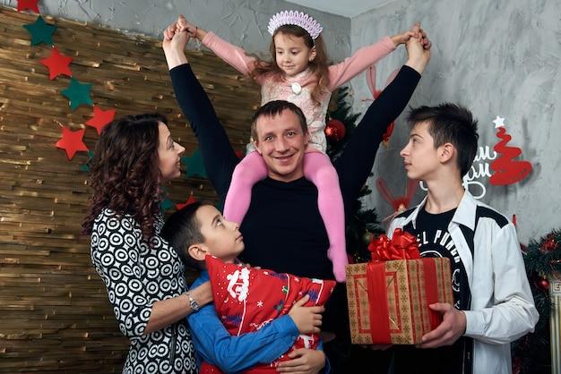 Gelukkig gezin: moeder, vader en drie kinderen bij de open haard voor de wintervakantie. kerstavond en oudejaarsavond.