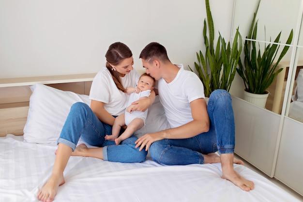 Gelukkig gezin: moeder, vader en zoon jongen liggen op een wit bed in de slaapkamer.