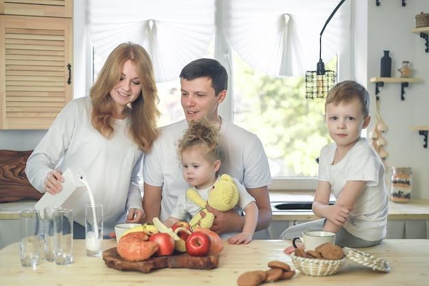 Gelukkig gezin moeder vader kind dochter en zoon thuis ontbijten moeder giet melk