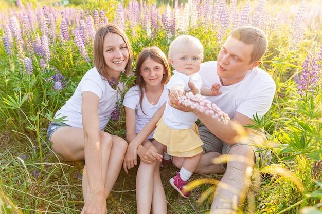 Gelukkig gezin moeder vader omarmen kinderen buiten. vrouw man baby kind en tienermeisje zittend op zomer veld met bloeiende bloemen achtergrond. gelukkige familie moeder vader en dochters spelen op weide.